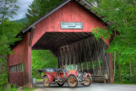 """Brookdale Cover Bridge, Stowe, VT This iconic covered bridge was built in 1964 and can be found along the bike path and Mountain Road. The structure includes wing walls. Barn red vertical ship-lapped boards cover the portals and sides. There are two opposing horizontal window openings along each side that run nearly the length of the bridge. The """"Brass 'n Gas"""" car is much older than the bridge. Stowe,"""